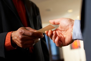 man giving business card to another man
