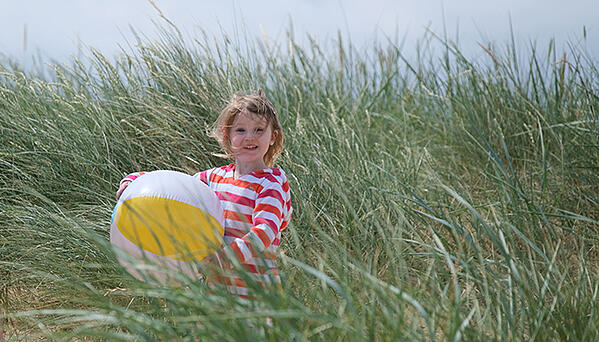 Child with ball standing in grass